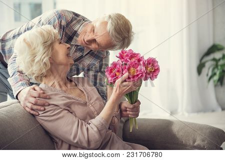 Delighted Retired Female Sitting On Sofa With Flowers In Hands. Old Man Standing Behind And Looking