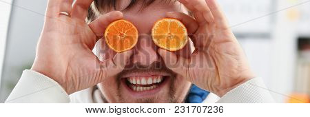 Male Hands Hold A Cut Fruit At Eye Level Instead Of Glasses. The Theme Of A Healthy Diet For Withdra