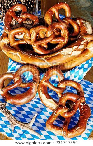 Closeup Of Bavarian Pretzels On Wooden Table With Blue White Bavarian Napkin