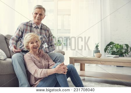 Portrait Of Content Senior Couple Enjoying Home Comfort. Man Is Sitting On Sofa And Woman Relaxing O