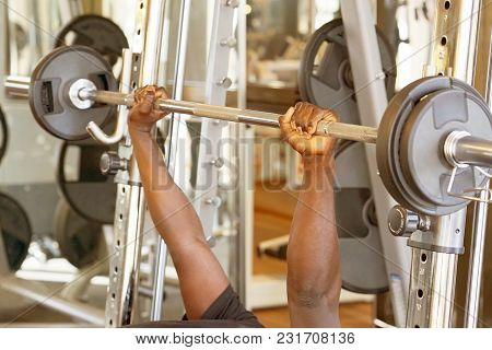 Hands Of A Young African Man Lifting A Bar In The Gym. Muscular Man Lifting A Barbell On Bench At Gy