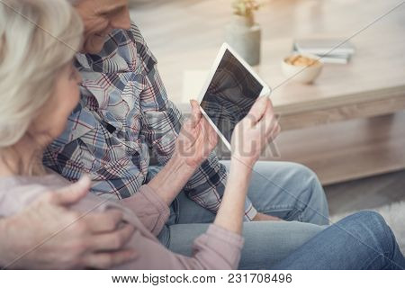 Glad Senior Wife And Husband Looking At Tablet While Resting Indoors. Focus On Female Hands With Gad