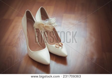 Beautiful Bridal Wedding Shoes With Engagement Rings Of The Bride And Groom On Wedding Day.