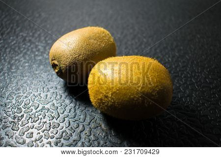Green Ripe Tropical Kiwi On A Plate On A Dark Black Background, Two Fruits.