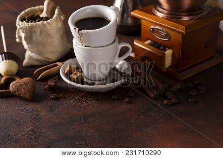 Cup Of Steaming Hot Coffee With Coffee Beans, Coffee Grinder, And Coffee Beans Bag On A Stone Brown