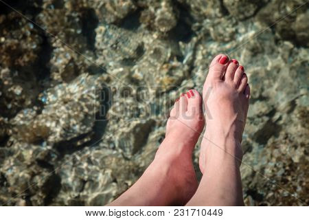 Close-up image of woman's feet over clear waters in British Virgin Islands