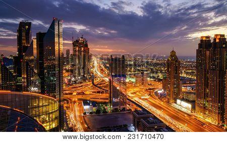 Bird's eye view of Dubai skyline and rush hour traffic in downtown at night