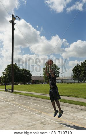New Orleans, Louisiana - June 16, 2014: Young Man Training Basketball In A Street Court In The City