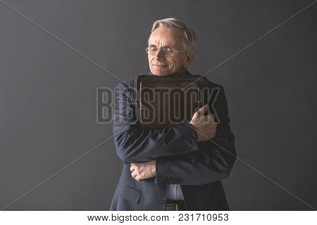 It Is My Favorite. Portrait Of Happy Senior Male Embracing Bag While Closing Eyes. Cheerful Worker C