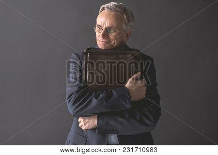 I Like My Job. Portrait Of Glad Old Businessman Hugging Suitcase. Friendly Employer Concept