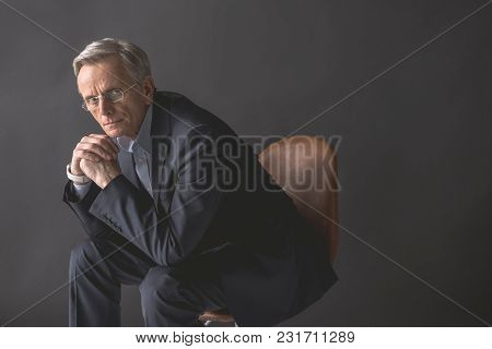 Portrait Of Thoughtful Mature Male Leaning On Arm While Looking At Camera. Demure Retire Worker Conc