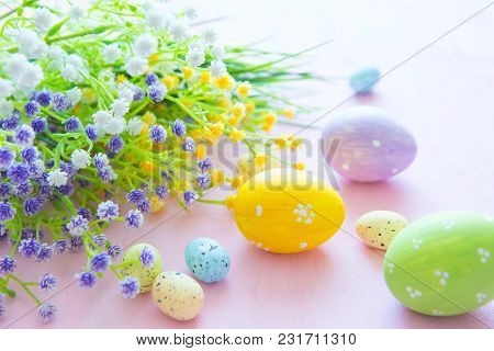 Spring Flowers With Easter Eggs On A Pink Wooden Background.
