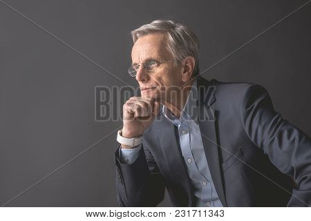 Side View Pensive Old Businessman Keeping Chin By Hand. Contemplative Senior Employer Concept. Copy