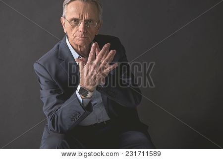 Serene Old Businessman Expressing Seriousness While Locating On Seat. Orderly Pensioner Concept