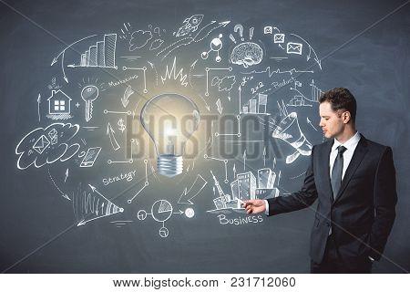 Presentation And Workshop Concept. Portrait Of Handsome European Businessman Standing On Chalkboard
