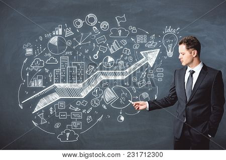 Presentation And Strategy Concept. Portrait Of Handsome European Businessman Standing On Chalkboard