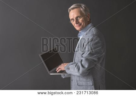 Portrait Of Outgoing Senior Male Demonstrating Display Of Notebook Computer While Typing In It. Mode