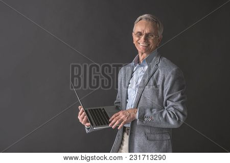 Portrait Of Outgoing Senior Male Typing In Notebook Computer While Holding It In Hand. Technology Co