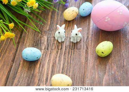 Rabbits With Easter Eggs On Wooden Table. Cute Little Easter Bunny.