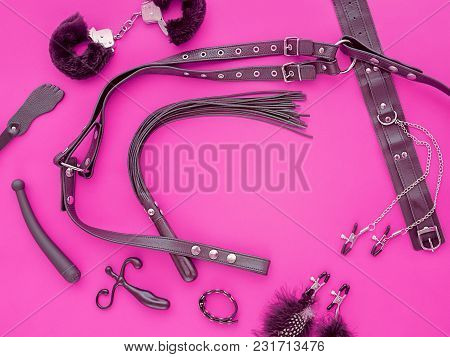 A Variety Of Sex Toys (whip, Leather Harness, Fur Handcuffs, Vibrator, Spanking Paddle And Other) Ar