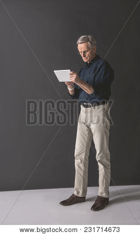 Full Length Portrait Of Serious Old Businessman Typing In Electronic Tablet While Keeping It In Arms