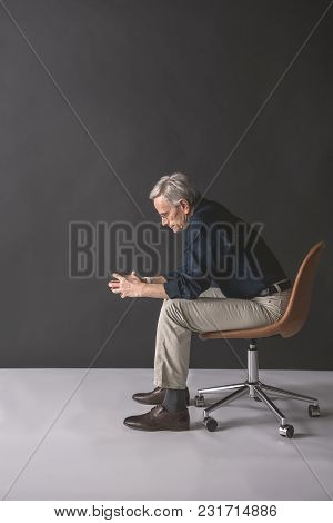 Full Length Side View Thoughtful Retire Male Sitting On Cozy Chair. Reverie Concept