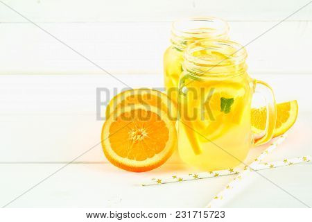 Orange Detox Water In Mason Jars On A White Wooden Table. Healthy Food, Drinks