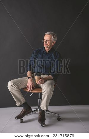 Full Length Portrait Of Beaming Old Businessman Drinking Cup Of Coffee While Locating On Chair. Glad