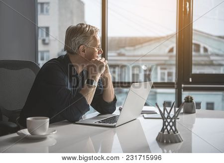 Pensive Mature Businessman Having Job With Laptop While Looking At Window. Contemplative Employer Co
