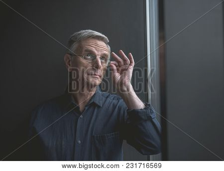 Portrait Of Pensive Old Businessman Holding Eyeglasses By Arm Indoor. Inspiration And Reverie Concep