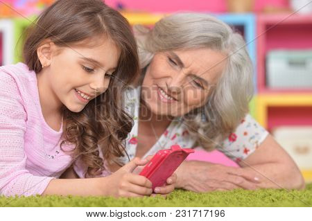 Smiling Granny With Her Granddaughter Using Smartphone