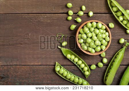 Fresh Green Peas In Wooden Bowl, Pods Of Green Peas, Top View