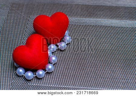 Two Hearts And Beads On A Textured Substrate.