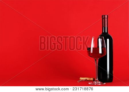 Wine Set On A Red Background - Bottle Of Wine With A Filled Glass On A Red Background, Space For Tex