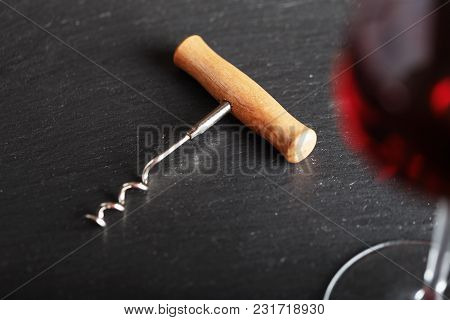 Red Wine In A Glass, Next To It Lies A Vintage Corkscrew, On A Black Background, Space For Text
