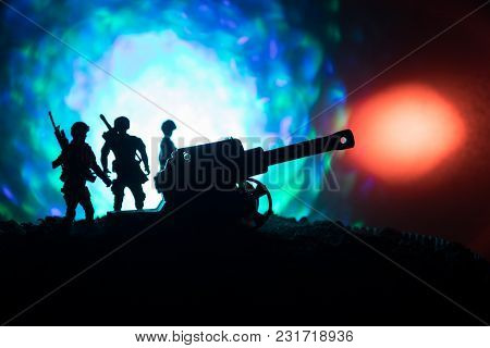 Battle Scene With Arillery And Standing Soldiers. Silhouette Of Old Field Gun Standing At Field Read