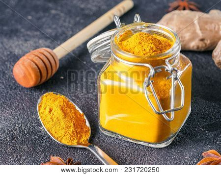 Dried Turmeric Powder In Glass Jar And Spoon On Black Cement Background. Ingredients For Golden Milk