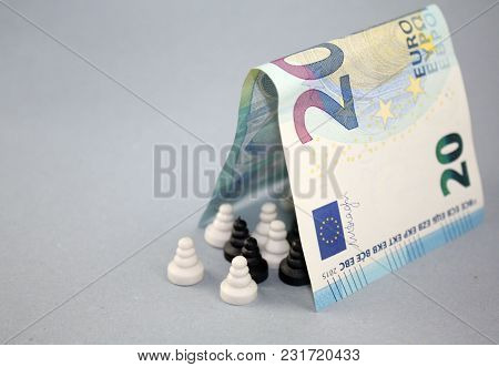 20 Euro Banknote As A Roof Over Black And White Chess Pawns, Concept Of Multicultural Europe, Tolera