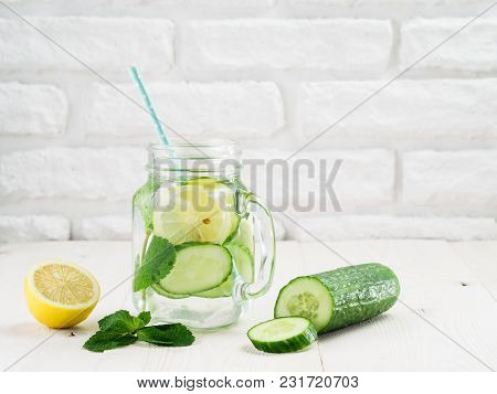 Infused Detox Water With Cucumber, Lemon And Mint In Glass And Jug On White Table. Diet, Healthy Eat