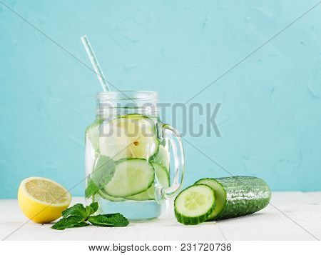 Infused Detox Water With Cucumber, Lemon And Mint In Glass Bottle On White Table. Diet, Healthy Eati