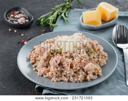 Raw Buckwheat Risotto With Chicken Meat And Rosemary Served Parmesan Cheese In Gray Plate On Black C