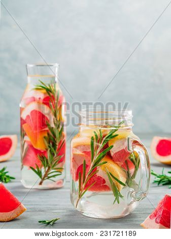 Infused Detox Water With Grapefruit And Rosemary In Mason Jar And Glass Bottle On Gray Wooden Table.