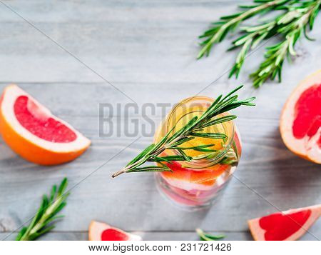 Infused Detox Water With Grapefruit And Rosemary In Glass Bottle On Gray Wooden Table. Diet Healthy