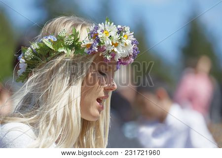 Vaddo, Sweden - June 23, 2017: Blonde Woman With Flowers In Her Hair Preparing To Celebrate The Swed