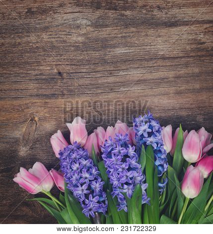 Pink Tulips And Blue Hyacinths Fresh Flowers On Dark Aged Wooden Table With Copy Space, Retro Toned