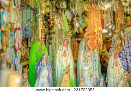 Fatima, Portugal - August 15, 2017: Close-up Of Statues Of Our Lady For Sale As Souvenirs In The Cat