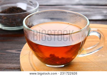 Hot Black Tea In A Glass Cup And Dry Tea On A Wooden Table