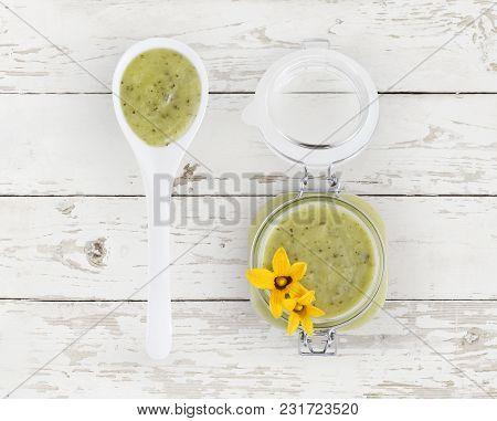 Zucchini Green Sauce In Jar With Flowers And Spoon Food Top View, Isolated On Wooden Table In Kitche
