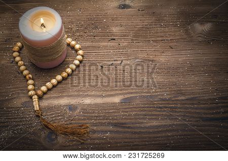 Beads And Burning Candle On Wooden Table Background With Copy Space. Meditation.