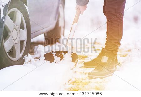 Man Dressed In Jacket Cleaning Snow Around His Car.